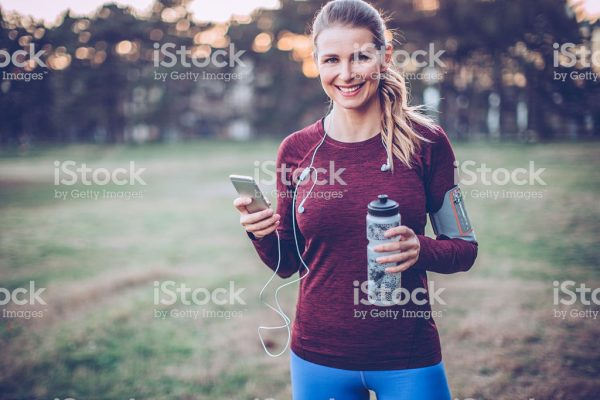 Young woman jogging outside at park. She took a break to rest. Holding her smart phone and headphones.